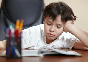 child bored doing work, falling asleep