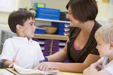 a-schoolboy-and-his-teacher-reading-in-a-primary-class_BFTsw0ASs