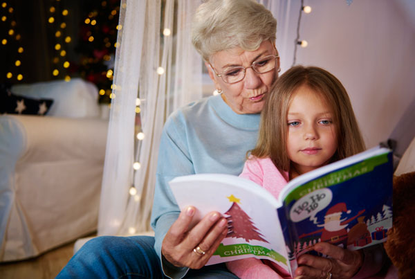 grandmother-and-granddaughter-reading-storybook-in-bed