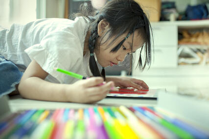 storyblocks-asian-children-playing-and-painting-color-pencil-on-paper-book-in-home-school_rWDMhfdPG