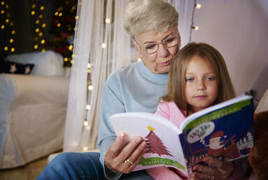 grandmother-and-granddaughter-reading-storybook-in-bed_BDEfa1ZYcz