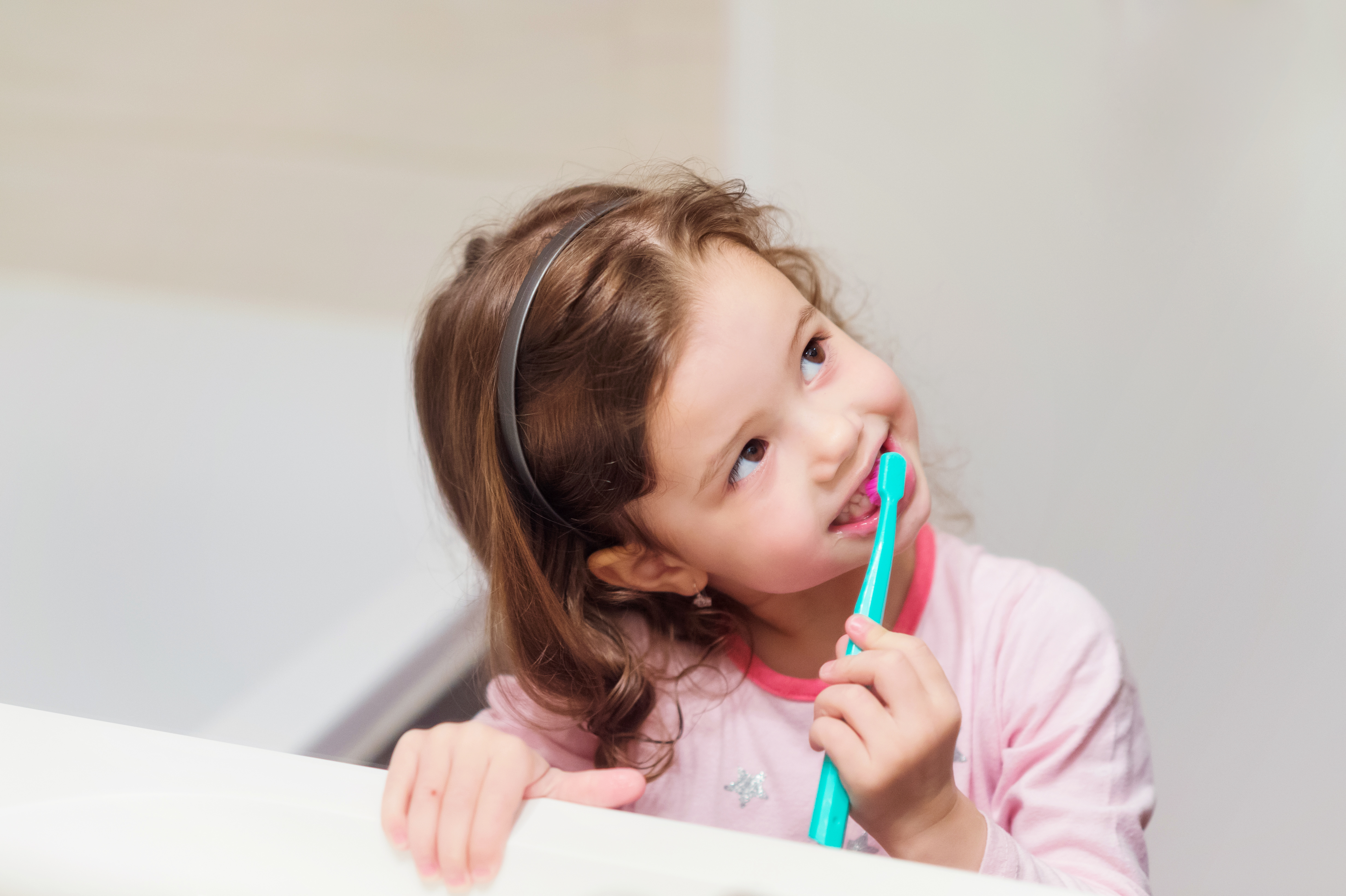little girl practicing her daily routine of brushing her teeth and gaining responsibility on a regular basis